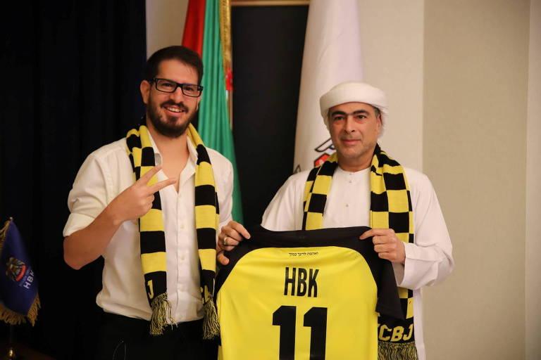 O xeque Hamad Bin Khalifa Al Nahyan e o proprietário do Beitar Jerusalem FC, Moshe Hovav, posam com a camisa do clube amarelo e preto