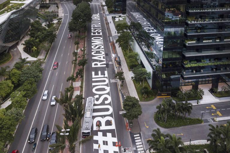 Intervenção do coletivo Nós Artivistas pinta na avenida Faria Lima, em São Paulo, a frase #Busque Racismo Estrutural diante do prédio do Google para lembrar o Dia Internacional dos Direitos Humanos, celebrado nesta quinta-feira (10)
