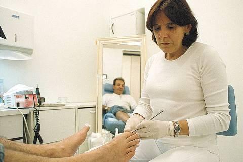 ORG XMIT: 504101_0.tif A podóloga Isabel Amorim, 49, prepara pés de paciente para aplicação do tratamento de órtese metálica para unha encravada. A órtese é uma prótese que atua como uma alavanca que força a unha em sentido contrário, corrigindo a curvatura da unha deformada. (São Paulo, SP, 26.09.2002. Foto: Fabiana Beltramin/Folhapress. Negativo 200211553)