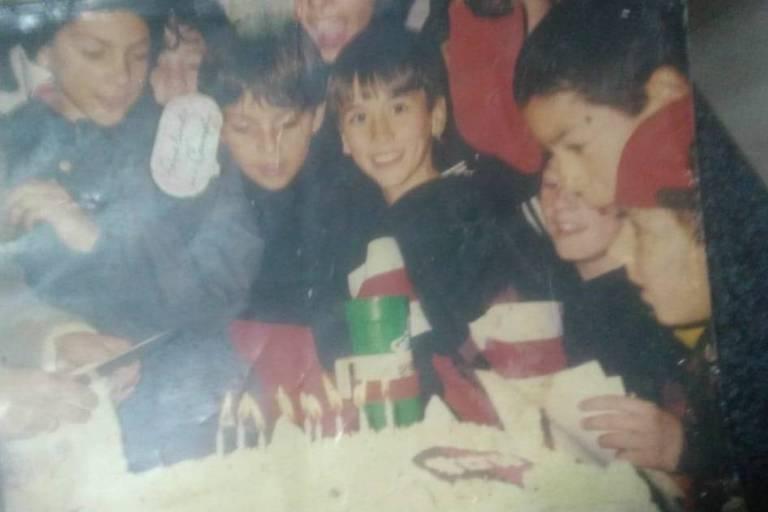 Sergio Maradona (centro) comemora aniversário com os amigos. À direita, Lionel Messi sorri enquanto olha para o bolo