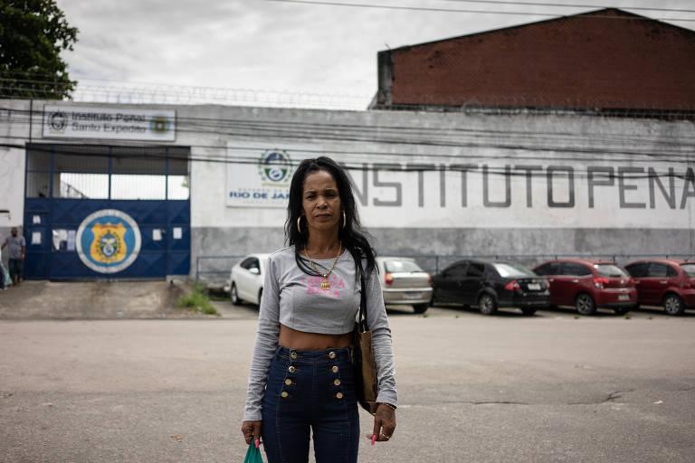 Mulher usa jeans e camiseta cinza em frente a muro branco e portão azul de presídio
