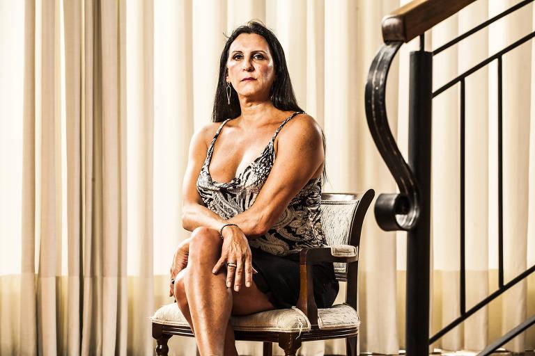 Mulher branca de cabelos pretos longos, vestindo blusa regata e saia, está sentada em cadeira e ao fundo cortina bege, ao lado corrimão.
