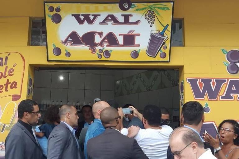 """Comitiva presidencial aglomerada diante de uma fachada em amarelo com letreiro roxo que diz """"Wal Açaí"""""""