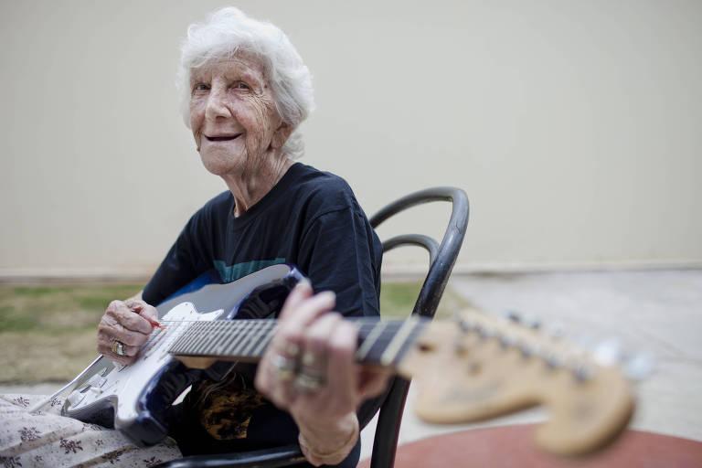 senhora branca idosa, de cabelos cursos muito brancos, está sentada em uma cadeira tocando guitarra e sorrindo