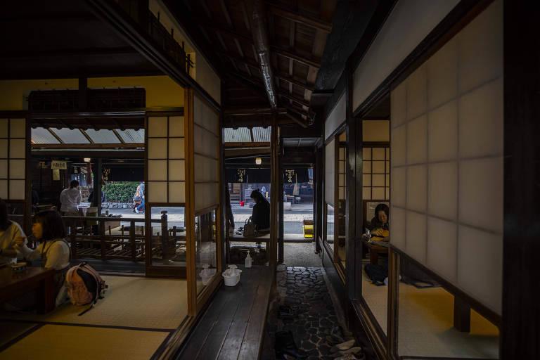 Vista interna de um restaurante japonês; clientes comem o bolinho japonês sentados no chão
