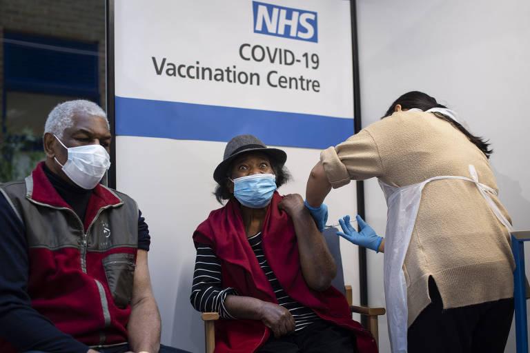 Lorna Lucas, 81, toma vacina contra a Covid-19 da Pfizer, antes de se marido, Winston, em hospital de Londres, na Inglaterra
