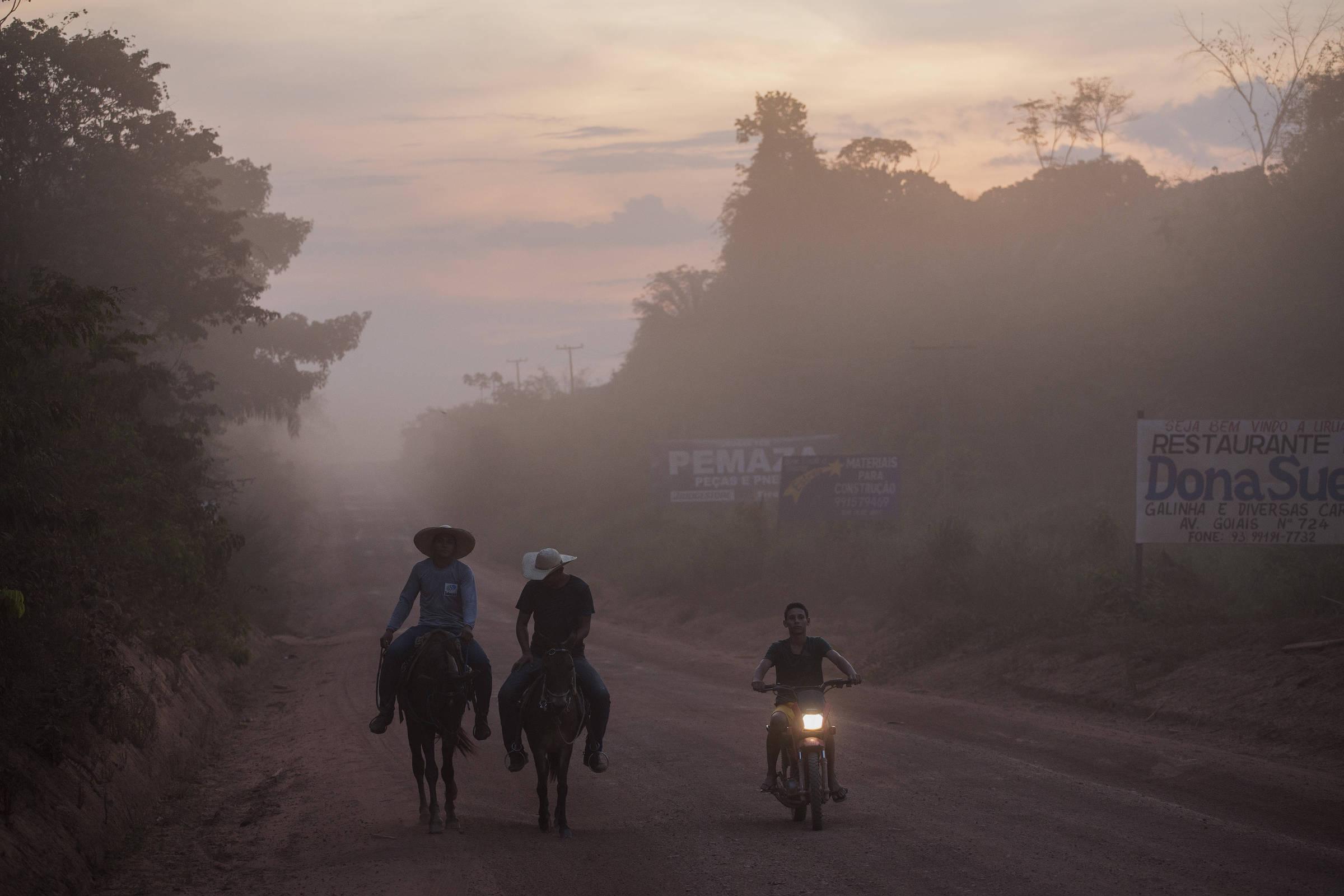 Vaqueiros e motoqueiro trafegam pela rodovia Transamazônica, próximo a Uruará, no Pará