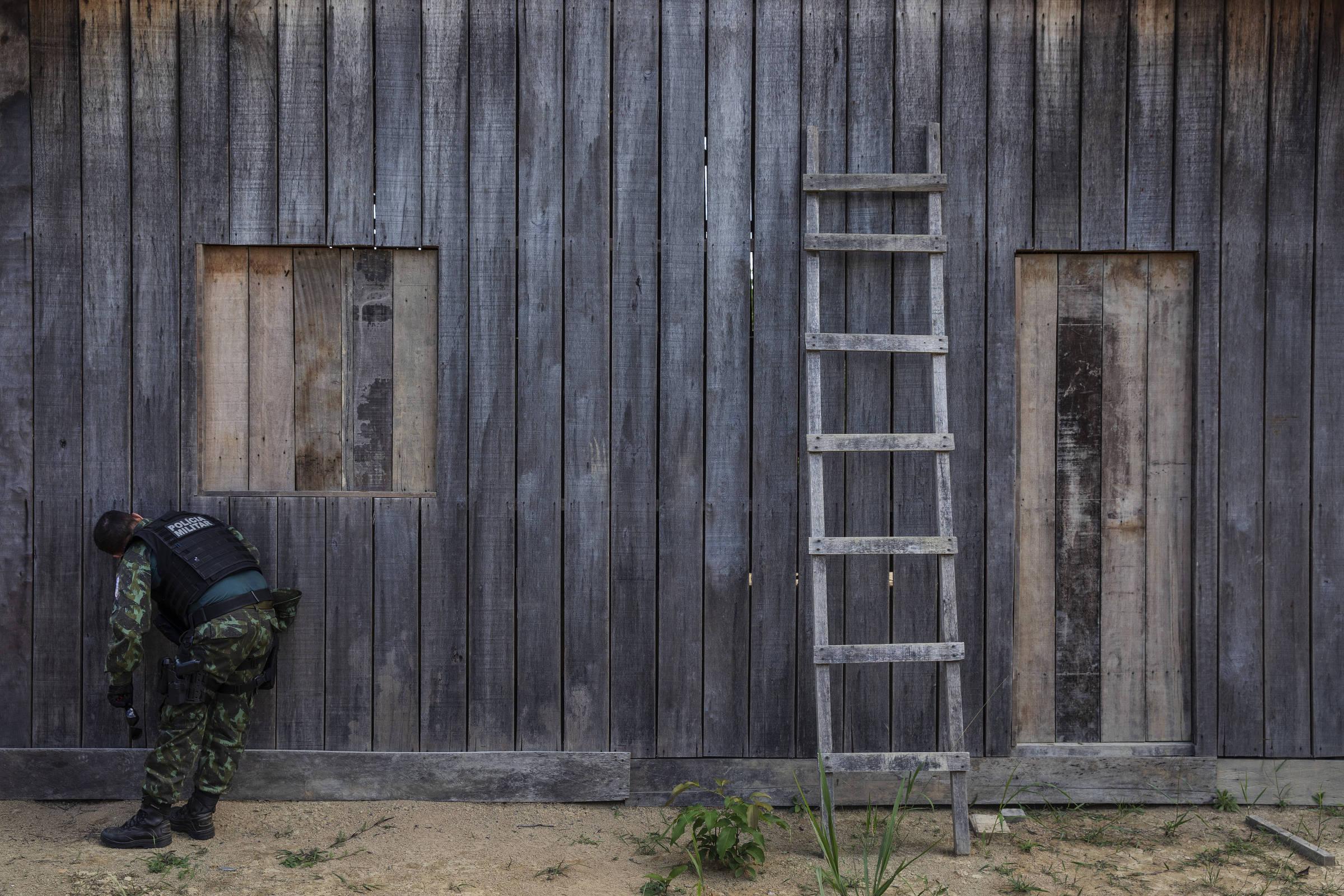 Policial militar espia o interior de um barracão localizado em uma área desmatada ilegalmente em Uruará