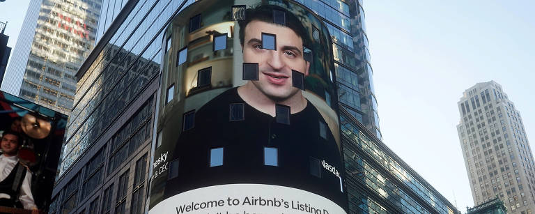 Telão em Manhattan, Nova York, apresentando Brian Chesky, presidente do Airbnb, no IPO da companhia na Nasdaq