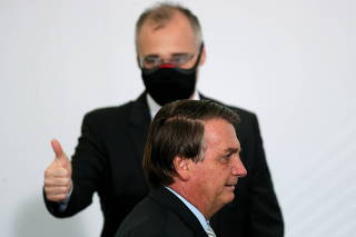 Brazil's Justice Minister Andre Luiz de Almeida Mendonca gestures next to Brazil's President Jair Bolsonaro after the opening of the forum 'Control in the Fight against Corruption 2020' at the Planalto Palace in Brasilia