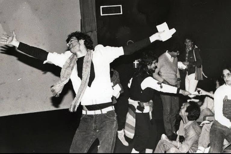 Foto em preto e branco mostra homem dançando com braços abertos