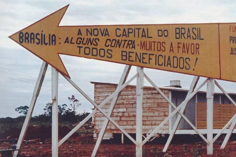 """Placa em formato de seta mostra a frase """"Brasília: a nova capital do brasil; alguns contra, muitos a favor; todos beneficiados!"""""""