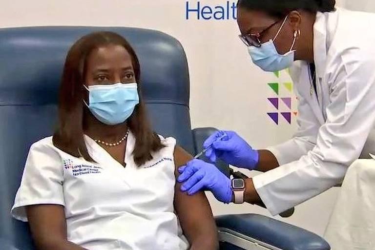 A enfermeira Sandra Lindsay está sentada, usa máscara e recebe a vacina da Pfizer nos EUA