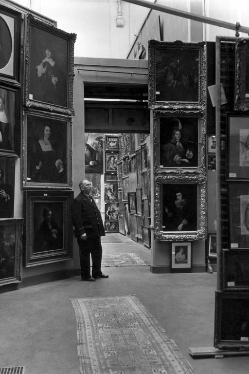 Homem olha muitos quadros de obra de arte