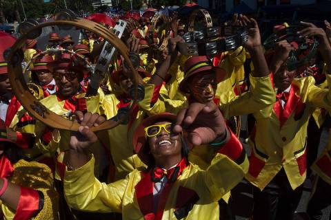 Performers take part in the annual Cape Town Minstrels Carnival, on January 2, 2016, in Cape Town.  This event dates back to the era of slavery in the Cape Colony, when the slaves were given the day off, on the day after New Year, January 2nd, and the slaves then celebrated with song and dance. Troupes of minstrels are formed, with bands of drummers and brass bands at the core, mostly in impoverished communities, in the Western Cape Province. They then practice during the year, make a troupe uniform, and then perform at this event, and other band competitions. More than 50 different troupes take part in this event.  / AFP / RODGER BOSCH ORG XMIT: RB004