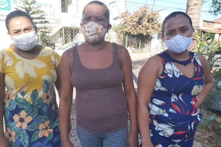 Valdênia da Silva (de amarelo), Naiara Sousa (de marrom) e Marília Gomes (de azul), usando máscaras, são moradoras do bairro Palmeira, em Fortaleza, beneficiadas pelos Bancos Comunitários Digitais durante a pandemia