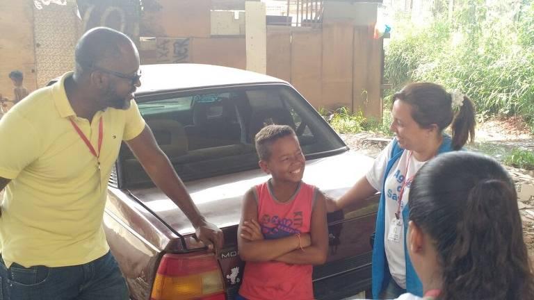 Homem conversa, apoiado em carro, com criança e duas mulheres