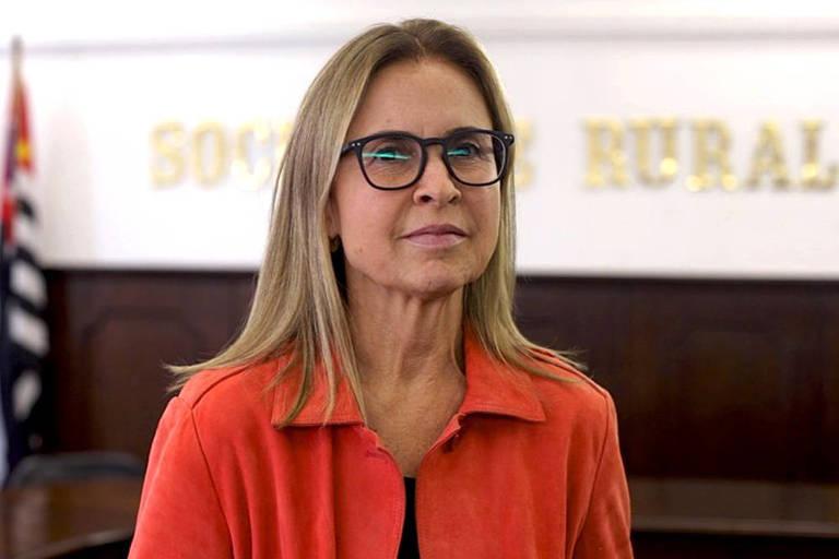imagem mostra mulher de blusa vermelha, com óculos, em auditório com bandeira de São Paulo no canto esquerdo