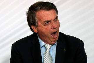 Brazil's President Jair Bolsonaro reacts during the opening of the forum 'Control in the Fight against Corruption 2020' at the Planalto Palace in Brasilia