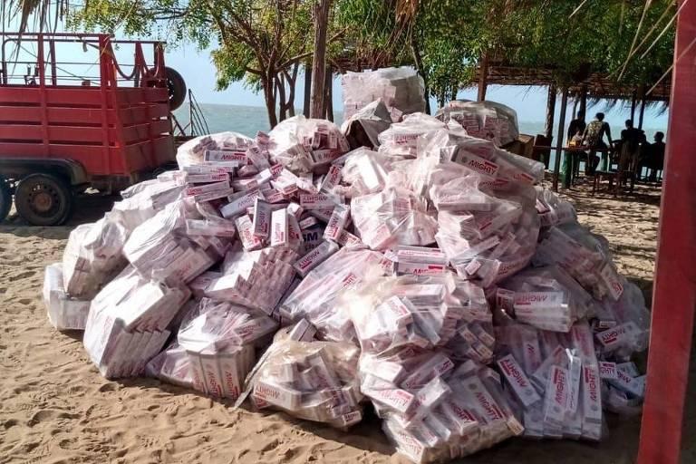 imagem mostra cargas de cigarro sobre a areia de uma praia do litoral do Piauí