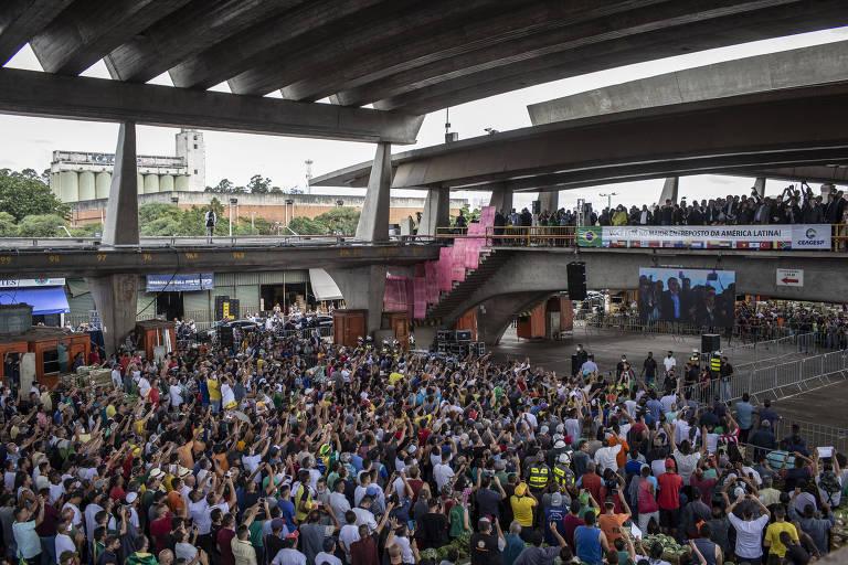 Foto mostra um grande galpão com uma multidão aglomerada, muitos sem máscara de proteção
