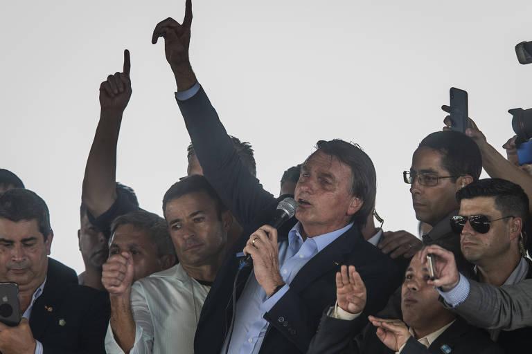 Ao lado do coronel Mello Araújo, presidente da Ceagesp, Bolsonaro alfinetou o governador João Doria (PSDB) e disse que não haverá mais corrupção na companhia; Bolsonaro discursa com o braço erguido em meio a outros homens