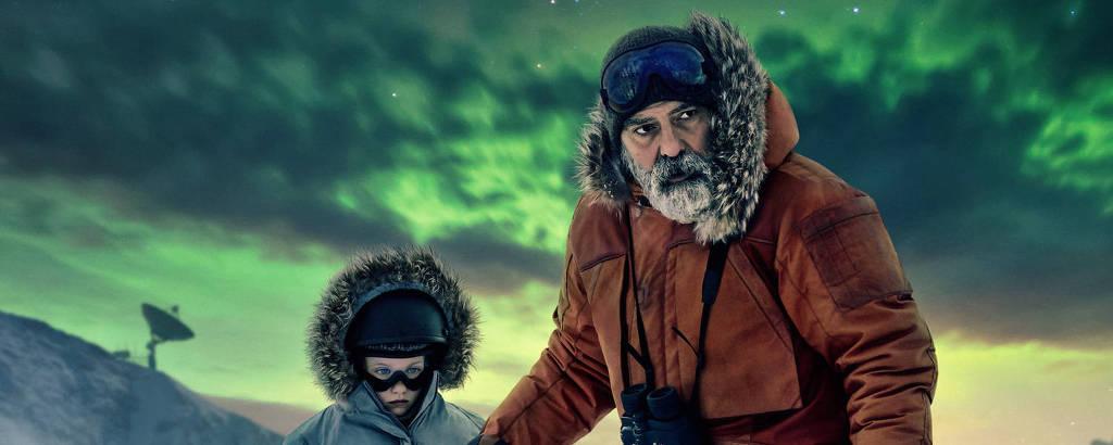 George Clooney e a atriz Caoilinn Springall olham adiante, com uma paisagem coberta de neve atrás