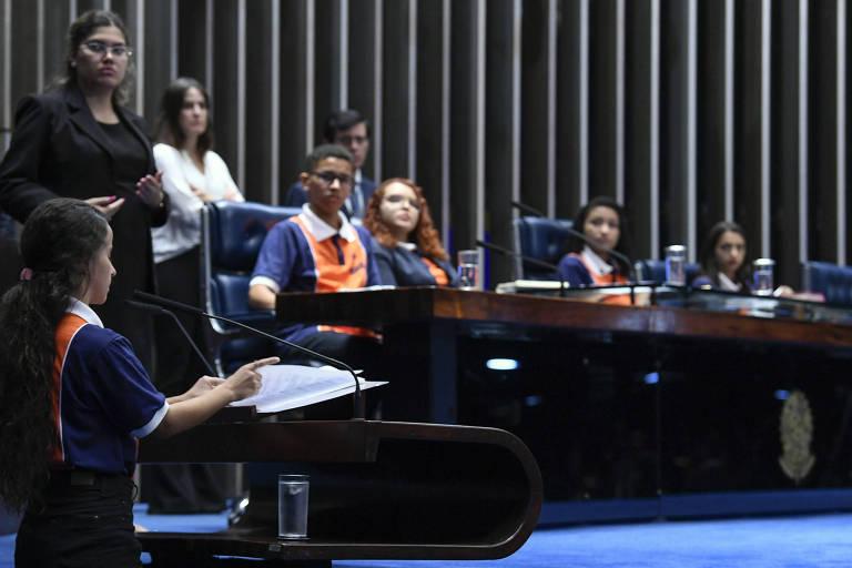 Uma menina discursa na tribuna. Na mesa, três meninas e um menino