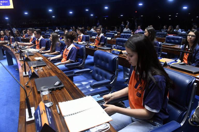 Jovens com camisetas laranjas no plenário