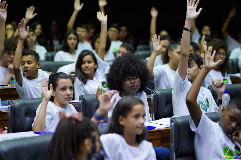 Estudantes com o braço erguido em votação no plenário