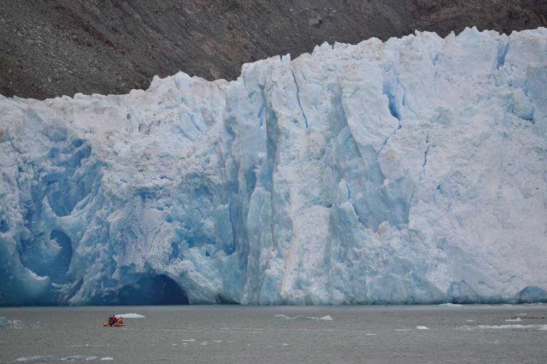Bote, bem pequeno, ao lado de geleira, em lago