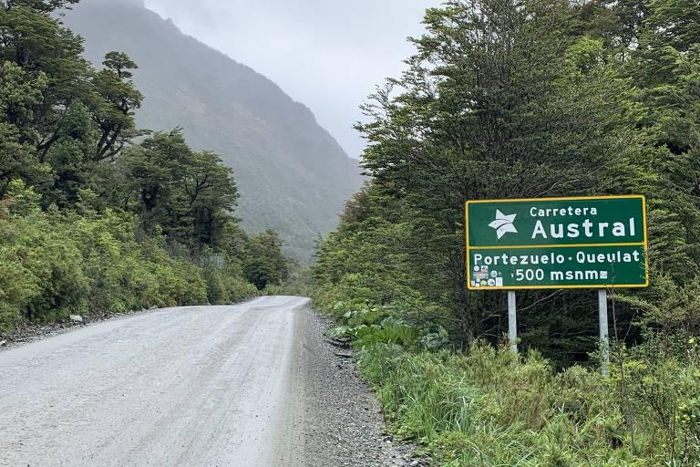 Estrada de terra com placa de sinalização e vegetação em volta