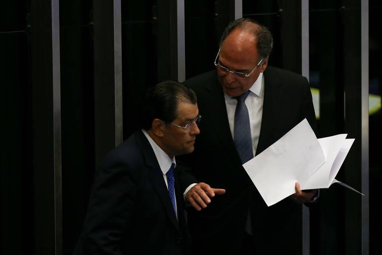 No plenário, Bezerra segura uma pilha de papéis enquanto fala com Braga, que o escuta
