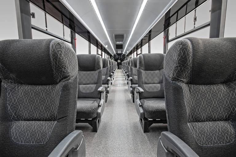 Interior de VLT (veículo leve sobre trilhos) é iluminado e contém duas fileiras de bancos pretos e cinzas