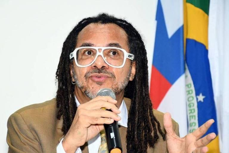 Homem negro falando ao microfone, veste terno bege, usa óculo, tem dreads de comprimento abaixo do ombro. Gesticula com uma das mãos enquanto fala. Ao fundo estão as bandeiras do Brasil e do estado da Bahia.