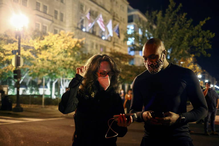 Dupla assiste pelo smartphone ao discurso do democrata Joe Biden, presidente eleito dos EUA, na Praça Black Lives Matter, próxima da Casa Branca, em Washington, enquanto os votos das eleições americanas são contados