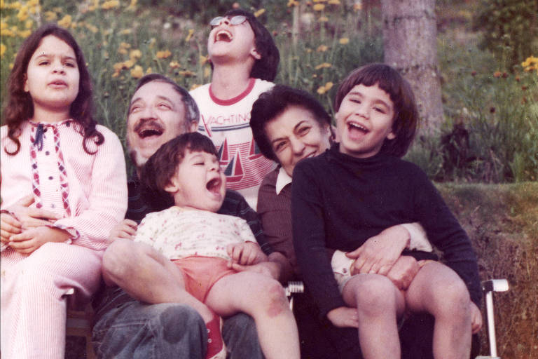 casal de homem e mulher idosos cercados por quatro crianças. eles estão sentados em cadeiras de praia num jardim e sorriem posando para a foto