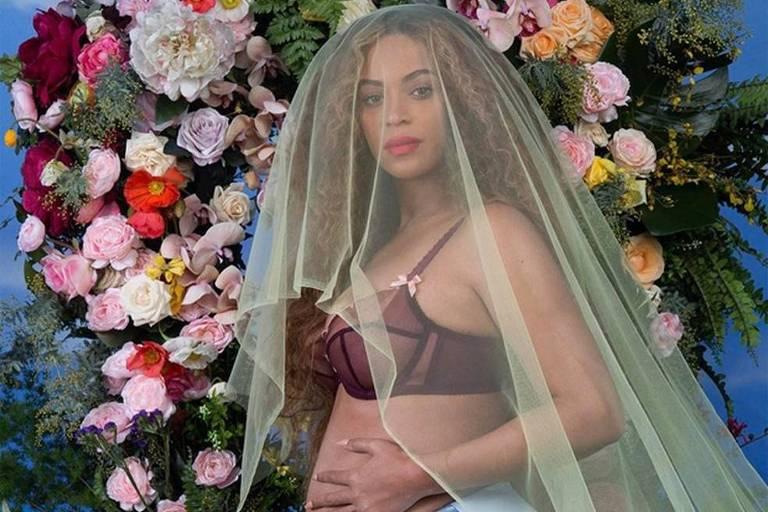 Beyoncé com a mão sobre a barriga coberta com um véu e cercada por flores