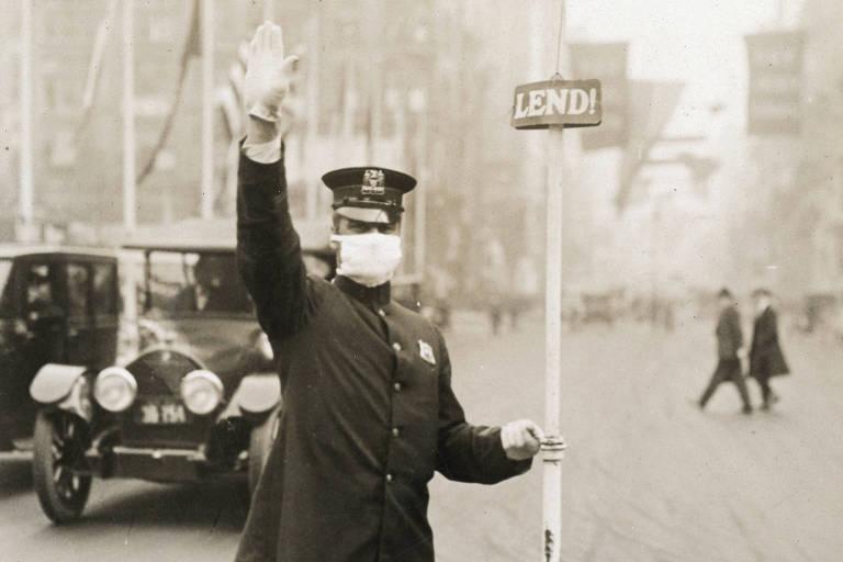 foto em preto e branco mostra policial de pé com máscara no meio da rua