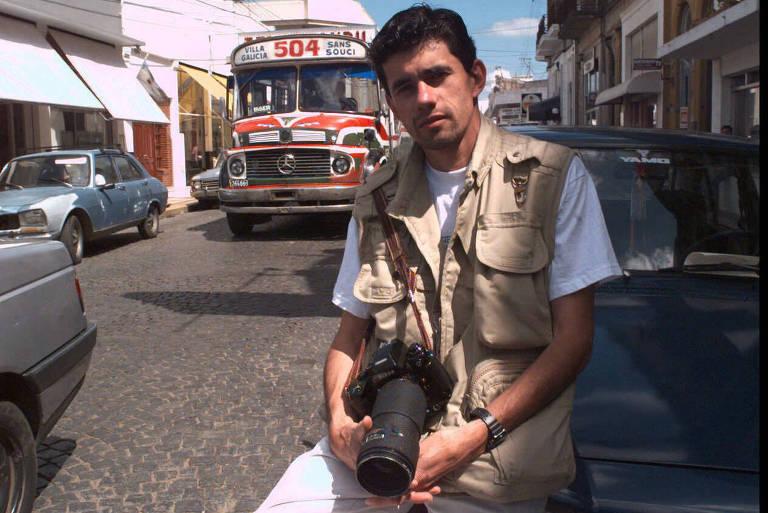 homem jovem se apoia em capô de carro estacionado na rua e segura uma câmera fotográfica profissional