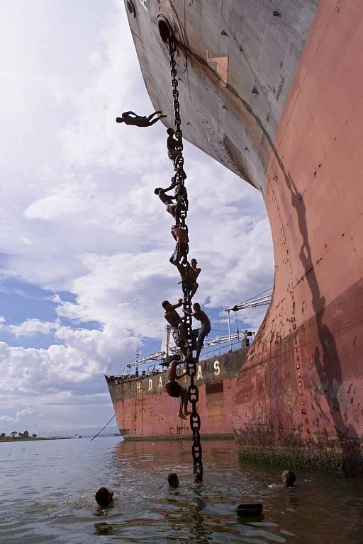 no canal portuário, meninos escalam a corrente da âncora de navio cargueiro atracado