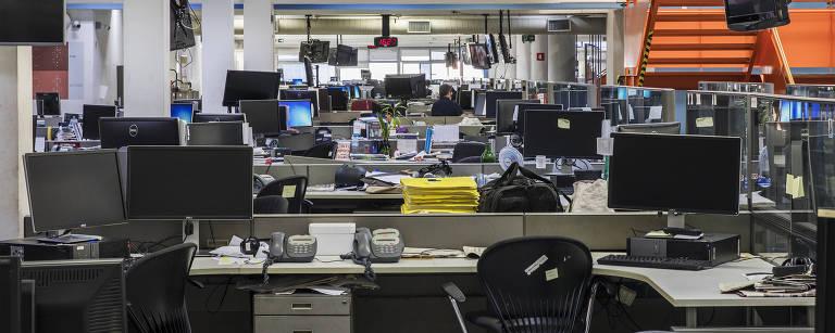 Dezenas de cadeiras e mesas, vazias, na Redação da Folha