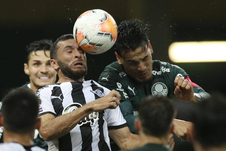 Gustavo Goméz, do Palmeiras, e Antonio Bareiro, do Libertad, batem cabeça com cabeça na partida de volta das quartas de final da Libertadoress, na última terça (15); ambos precisaram ser atendidos dentro de campo, com cortes na região da pancada
