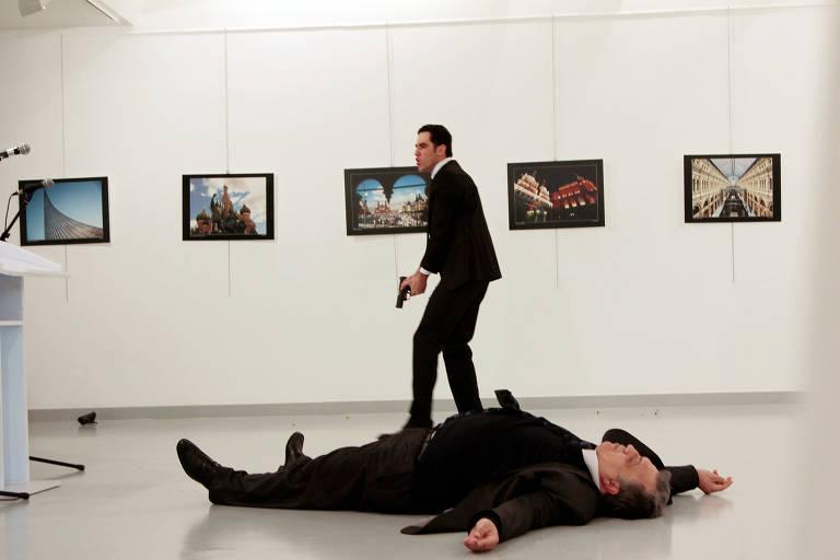 O embaixador russo Andrei Karlov está deitado no chão enquanto um homem segura um revólver no fundo da imagem, em uma galeria de arte com quadros expostos ao fundo