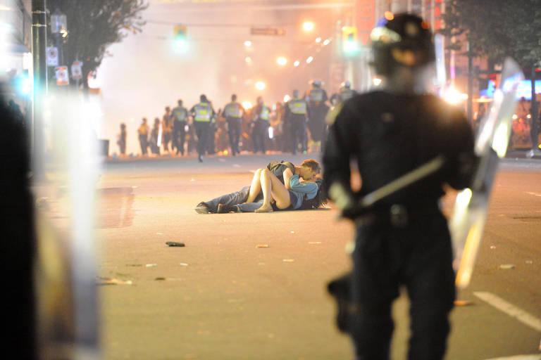 Casal se beija no chão durante um confronto entre policiais e torcedores em Vancouver, no Canadá