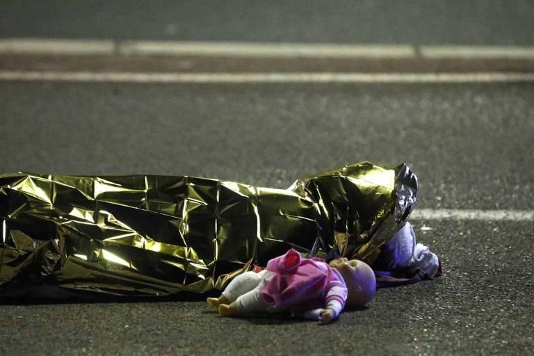 Corpo de menina morta, coberto com uma manta dourada, ao lado de uma boneca, após o atentado em Nice, na França, durante as comemorações do Dia da Bastilha