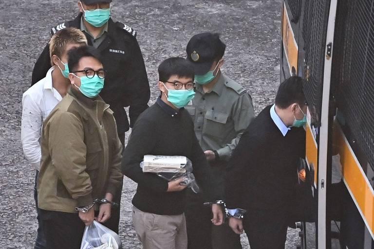 Joshua Wong (centro) e outros ativistas entram em van policial antes de serem sentenciados à prisão