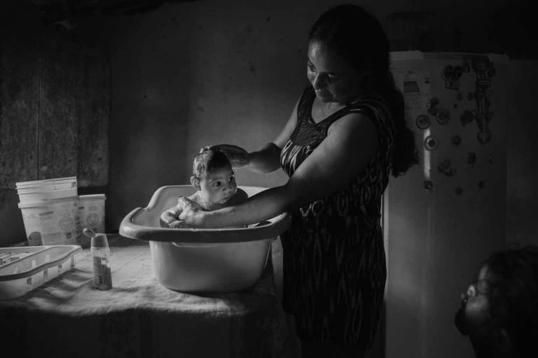 Adriana Cordeiro Soares dá banho em seu filho João Miguel, 3 meses na época, que nasceu com microcefalia, em sua casa na zona rural de São Vicente do Seridó, na Paraíba