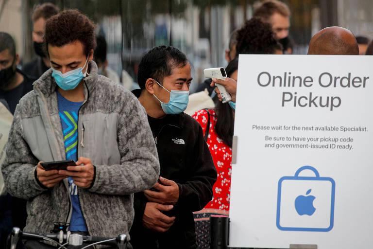 Clientes testam a temperatura enquanto esperam na fila do lado de fora da Apple Store do Brooklyn, em Nova York, para receber os aparelhos do novo iPhone 12 durante a pandemia de coronavírus