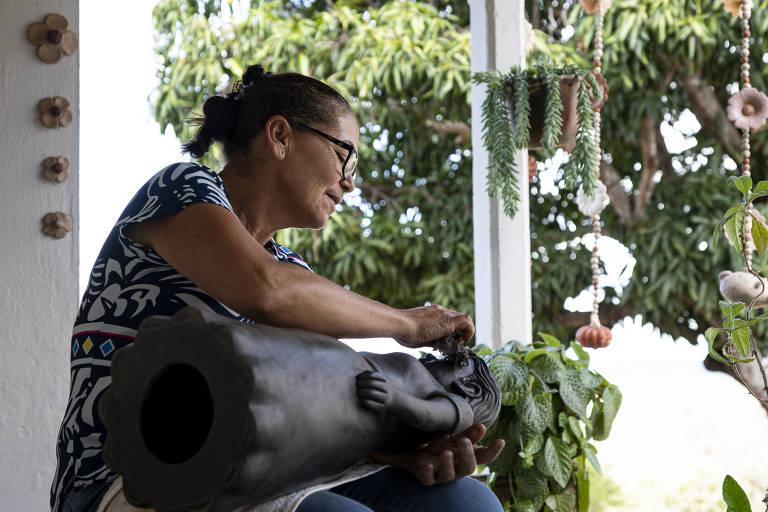 Senhora trabalha em boneca de cerâmica, que está em seu colo